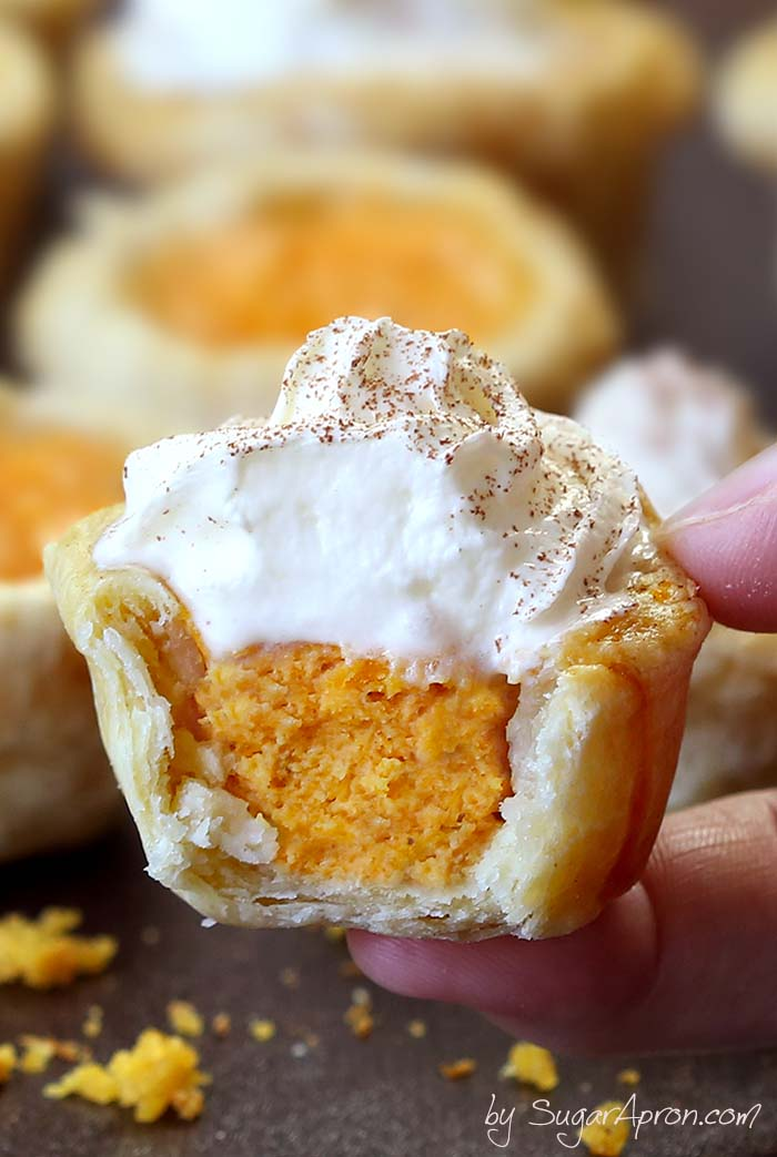 A small pumpkin pie bite topped with whipped cream is held between two fingers with more bites blurrily visible in the background.