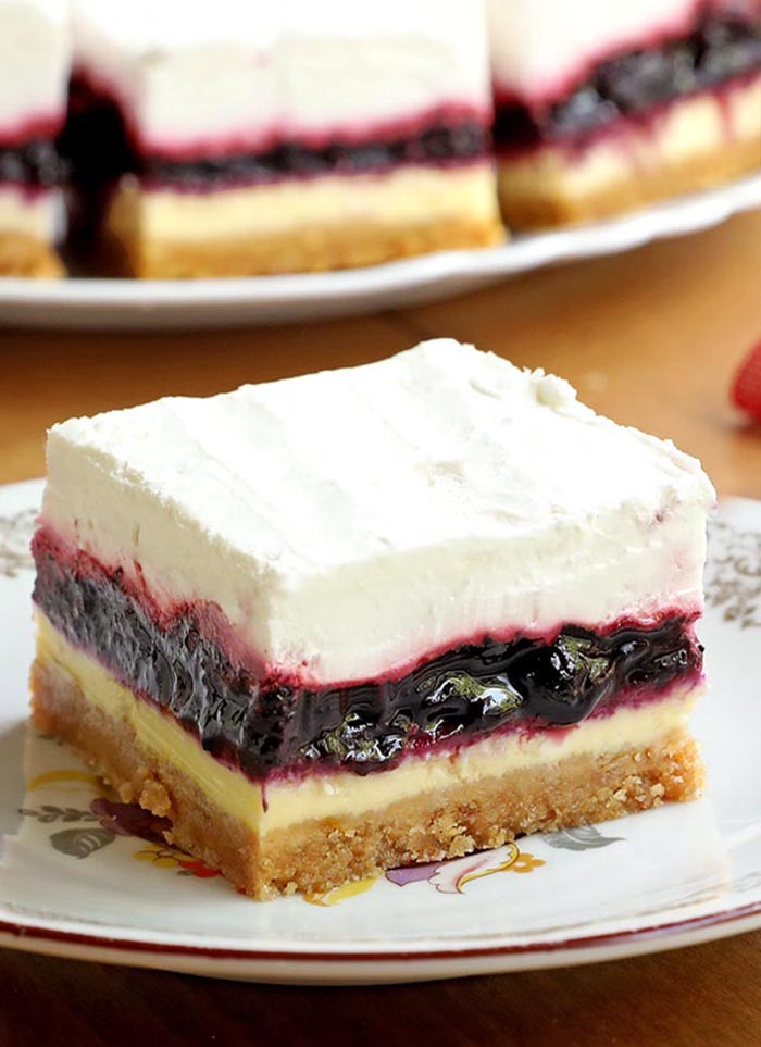 Blueberry Cheesecake Dessert with a light and creamy cheesecake topped with blueberry pie filling and whipped cream would be a perfect summertime treat for your family.